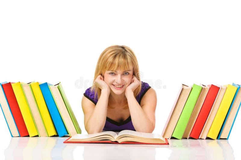 Stående av en ung deltagareläsning en boka som ligger på en däcka fotografering för bildbyråer