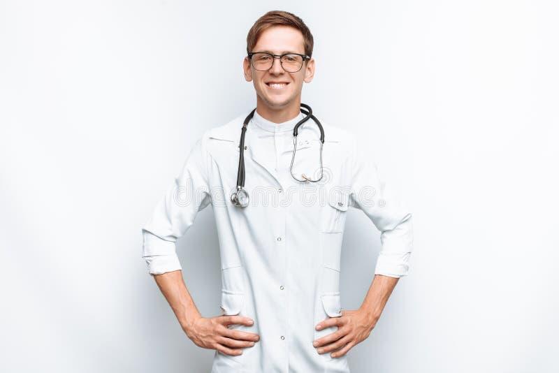 Stående av en ung doktor på en vit bakgrund, allmäntjänstgörande läkare i studion, med en stetoskop på halsen arkivfoton