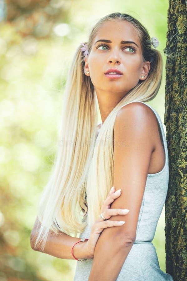 Stående av en ung drömmarekvinna i naturen Långt blont hår, gröna ögon arkivbilder
