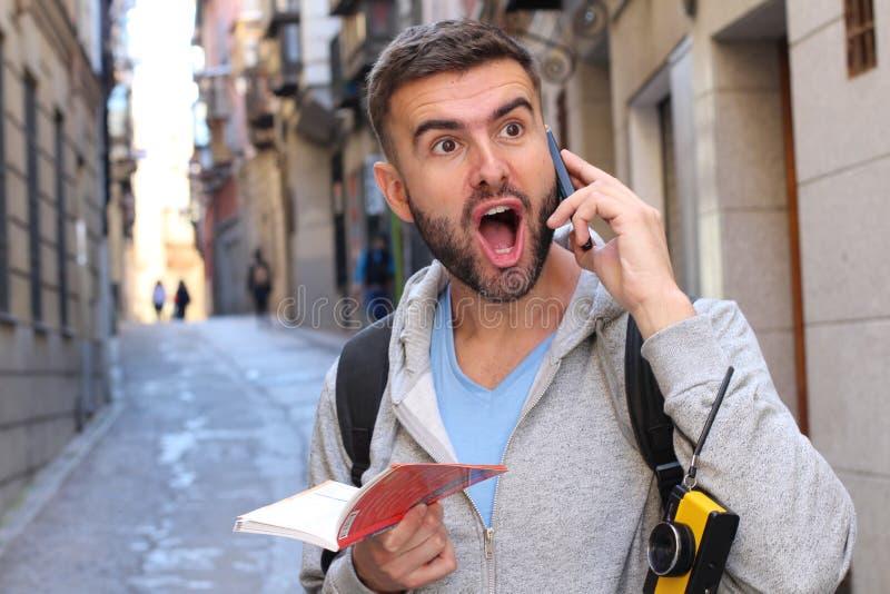 Stående av en ung förvånad man som talar på telefonen arkivbild