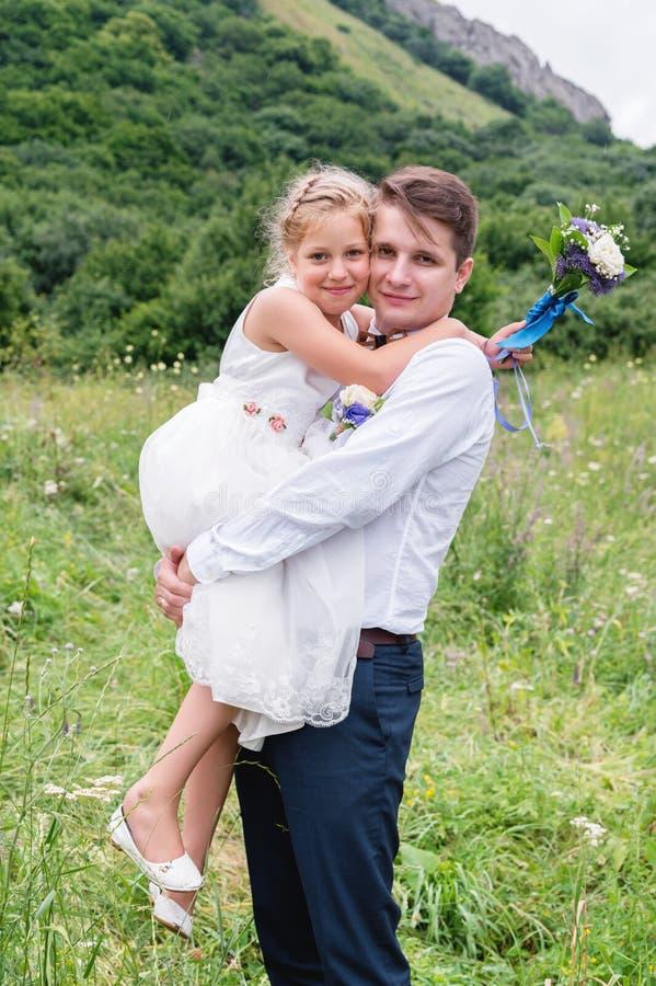 Stående av en ung fader med hans dotter i hans armar arkivfoto
