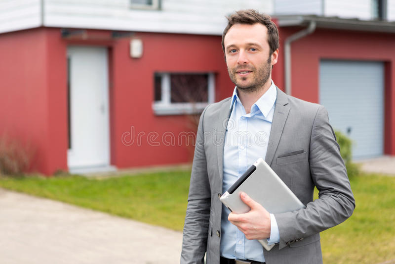 Stående av en ung fastighetsmäklare framme av ett hus arkivbild