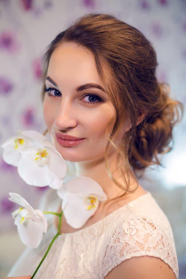 Stående av en ung flicka i den vita klänningen med en orkidéblomma royaltyfri fotografi