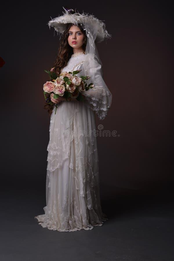 Stående av en ung flicka i en vit hatt arkivbilder
