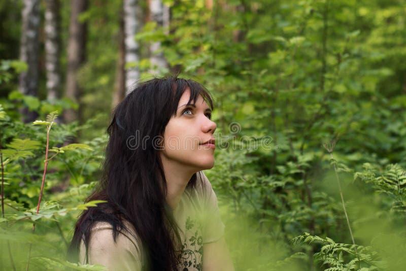 Stående av en ung flicka i ett Forest Park bland grönt gräs royaltyfria bilder