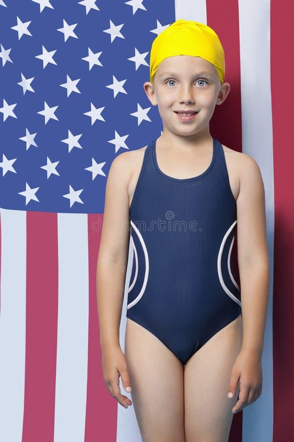 Stående av en ung flicka i swimwear som framme står av amerikanska flaggan royaltyfri foto
