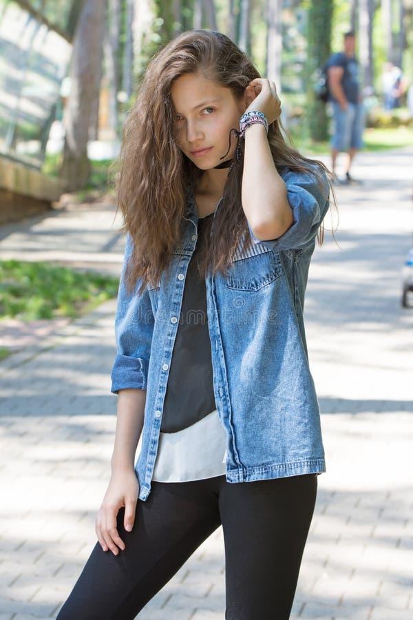 Stående av en ung flicka med långt hår med armbandet på hans arm i grov bomullstvillskjorta royaltyfri fotografi