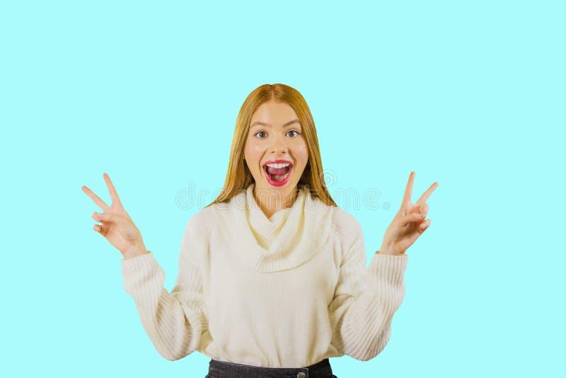 Stående av en ung flicka med långt rött hår som visar piss med båda händer som rymmer upp dem och entusiastiskt ler royaltyfria bilder