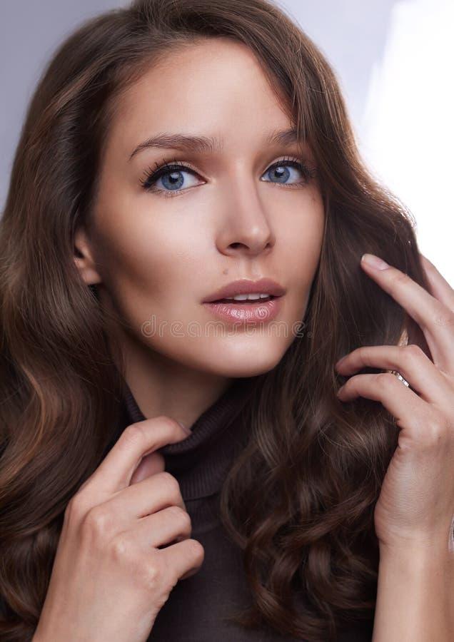 Stående av en ung flicka med perfekt hud och makeup, med lockigt mörkt hår royaltyfri foto