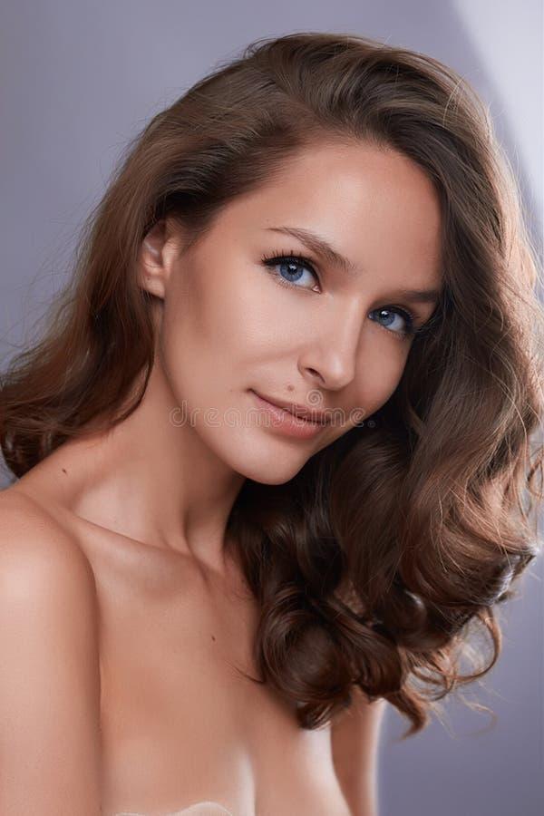 Stående av en ung flicka med perfekt hud och makeup, med lockigt mörkt hår royaltyfria foton
