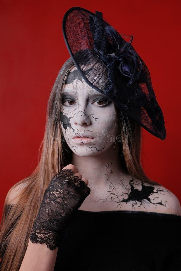 Stående av en ung flicka med smink i stilen av allhelgonaaftonen Svartsprickor målas på den kvinnliga framsidan och förkroppsliga fotografering för bildbyråer