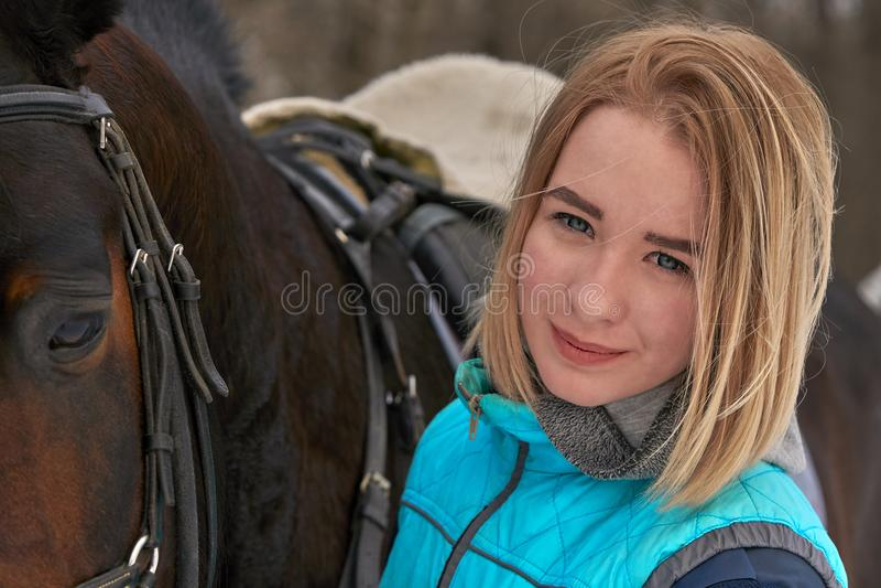Stående av en ung flicka med vitt hår bredvid en brun häst Flickan rymmer hästen Närbild royaltyfri fotografi