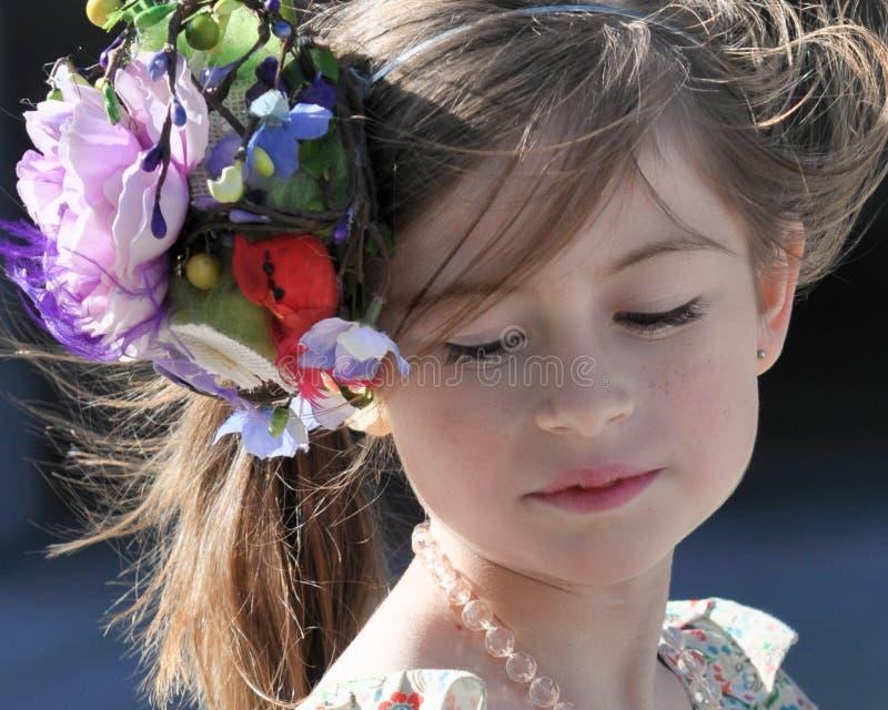 Stående av en ung flicka och att bära en hatt som nedåt stirrar royaltyfri foto