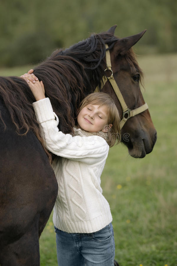 Stående av en ung flickamodell som kramar horse&en x27; s-hals med hans stängda ögon livsstil royaltyfri fotografi