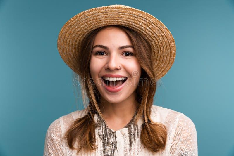 Stående av en ung gladlynt flicka i sommarhatten som isoleras över blå bakgrund, royaltyfria bilder