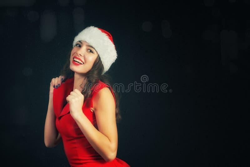 Stående av en ung gladlynt kvinna i jultomten hatt arkivfoton