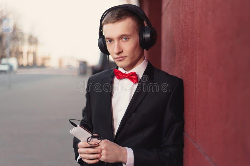 Stående av en ung grabb i en svart dräkt och en röd fluga man som lyssnar till musik i stor hörlurar fotografering för bildbyråer