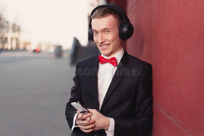 Stående av en ung grabb i en svart dräkt och en röd fluga Man som lyssnar till musik i stor hörlurar royaltyfria foton