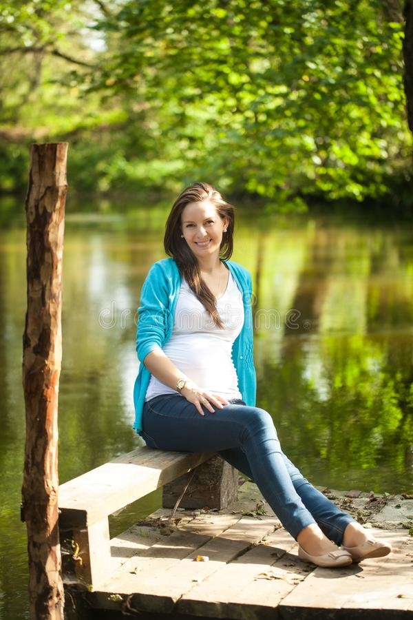 Stående av en ung gravid kvinna nära floden arkivfoton