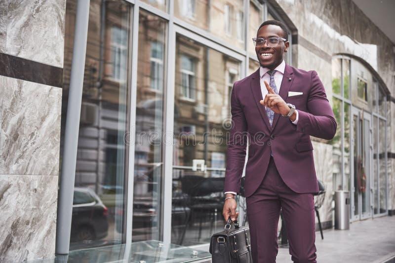 Stående av en ung härlig afrikansk amerikanaffärsman med en portfölj samtal för möte för bärbar dator för skrivbord för affärsaff royaltyfria bilder