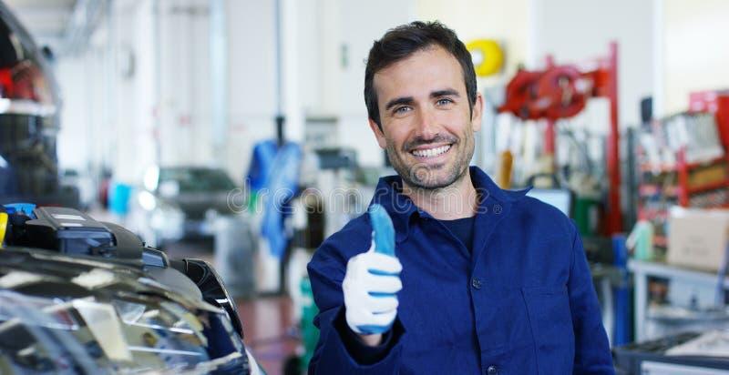 Stående av en ung härlig bilmekaniker i ett bilseminarium, i bakgrunden av en reparation för bilservicebegrepp av maskiner, fel royaltyfri foto