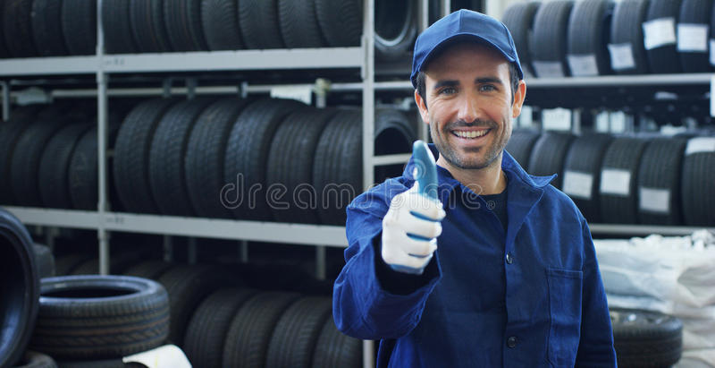 Stående av en ung härlig bilmekaniker i ett bilseminarium, i bakgrunden av en reparation för bilservicebegrepp av maskiner, fel royaltyfria foton