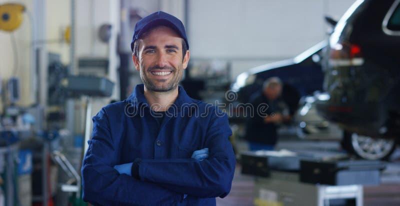 Stående av en ung härlig bilmekaniker i ett bilseminarium, i bakgrunden av service Begrepp: reparation av maskiner, feldiameter royaltyfri foto