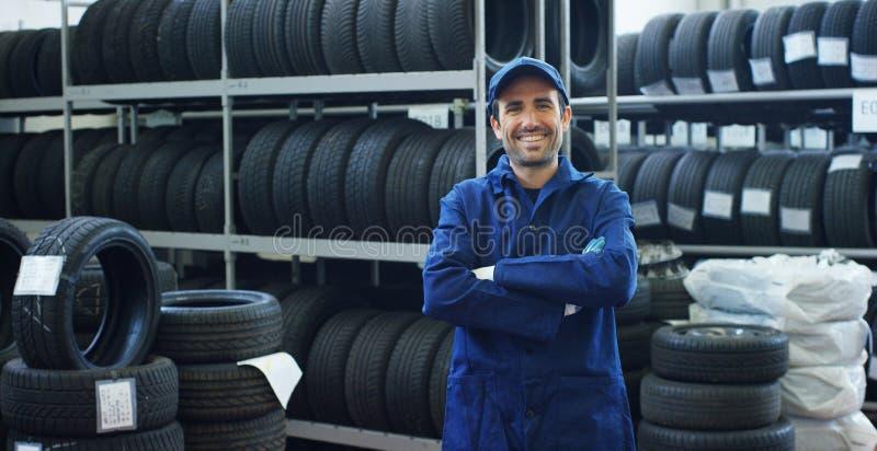 Stående av en ung härlig bilmekaniker i ett bilseminarium, i bakgrunden av service Begrepp: reparation av maskiner, feldiameter arkivfoto