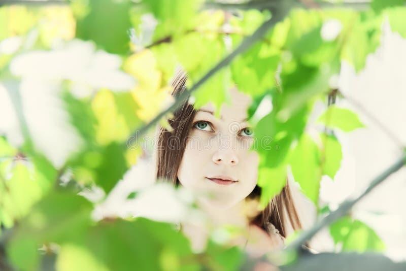 Stående av en ung härlig flicka i lövverket fotografering för bildbyråer