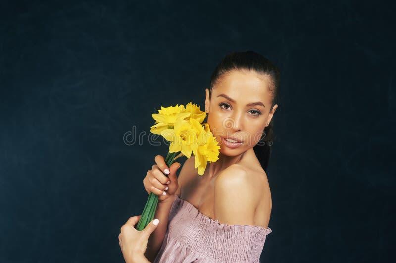 Stående av en ung härlig flicka med blommor i studion arkivbild