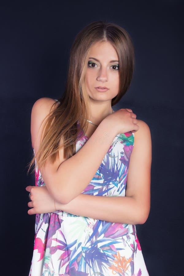 Stående av en ung härlig flicka med långt hår i en vit klänning med blommor i studion på en svart bakgrund fotografering för bildbyråer