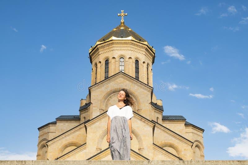 St?ende av en ung h?rlig flicka mot bakgrunden av Tsminda Sameba, en forntida Christian Church i Georgia royaltyfria foton
