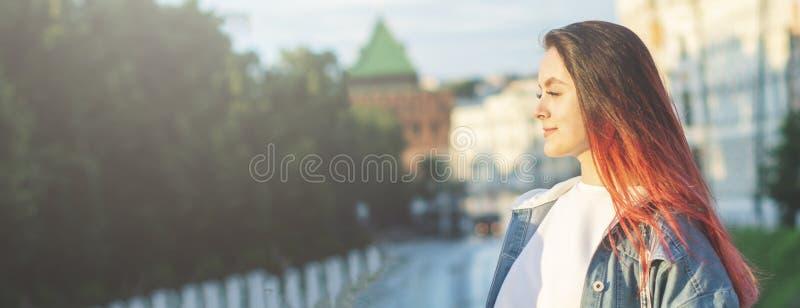 Stående av en ung härlig flickastudent med ett lyckligt leende på gatan på en sommardag baner arkivbilder