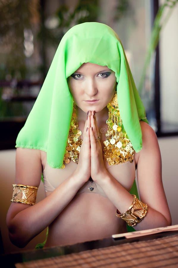 Stående av en ung härlig kvinna i en bönposition arkivbild