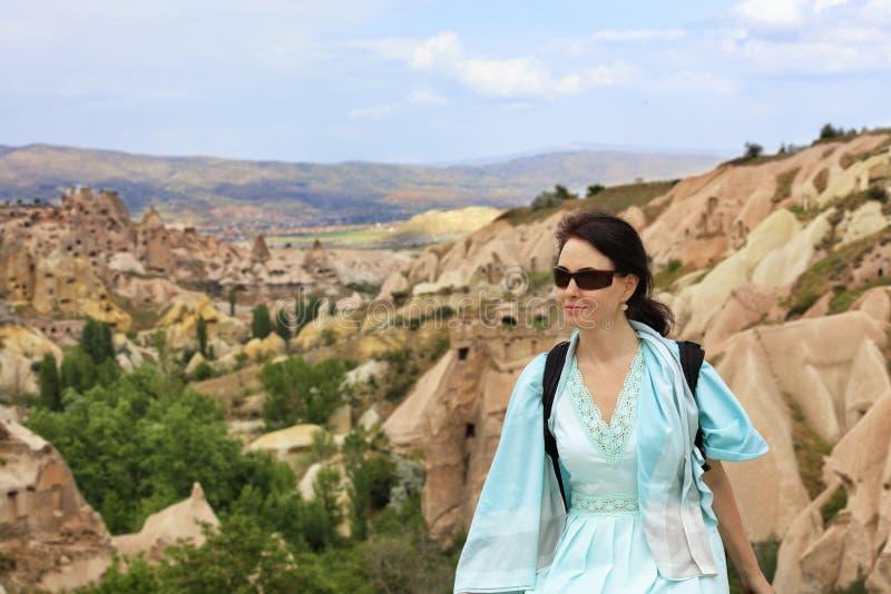 Stående av en ung härlig kvinna i en turkosklänning mot bakgrunden av ett suddigt landskap av bergdalar och royaltyfria foton
