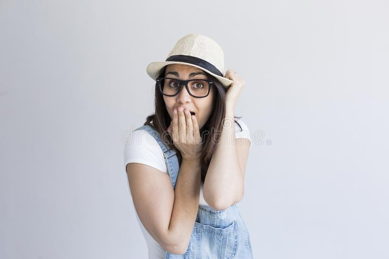 stående av en ung härlig kvinna med den moderna exponeringsglas och hatten Vit bakgrund millennial Hipster och livsstil Framställ royaltyfri bild