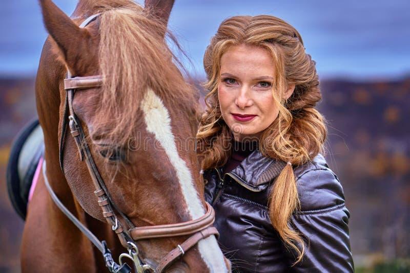 Stående av en ung härlig kvinna med långt brunt hår Kvinnan på en häst går royaltyfria foton