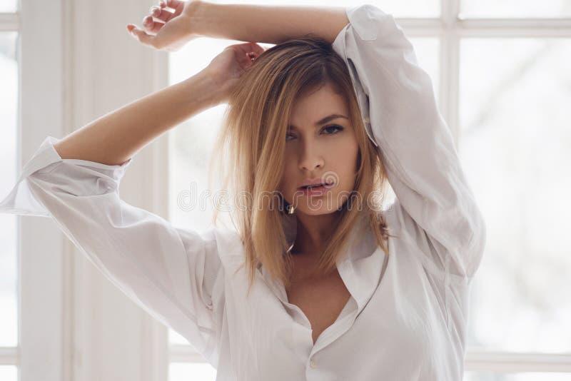Stående av en ung härlig kvinna på fönstret Flicka i vitskjorta arkivbilder