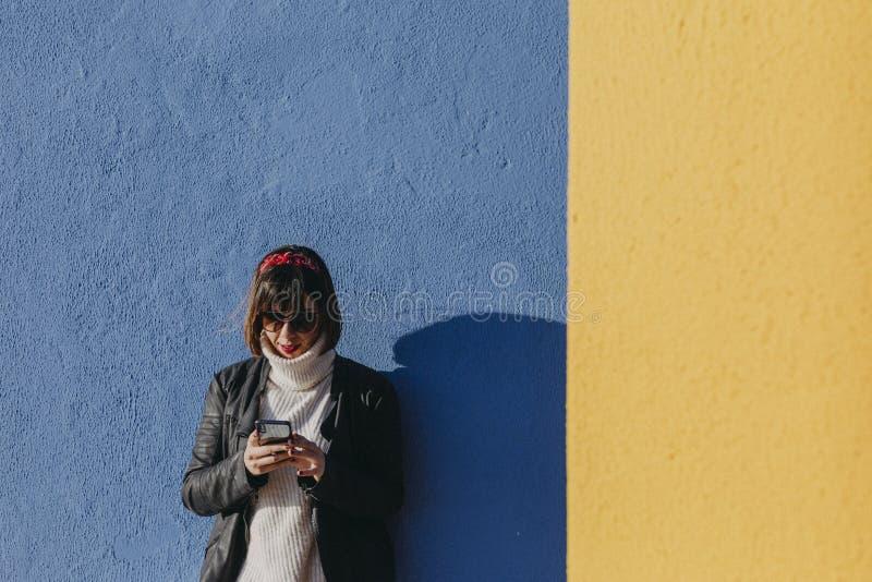 stående av en ung härlig kvinna som använder utomhus mobiltelefonen över blå och gul bakgrund Livsstil och roligt begrepp royaltyfri fotografi