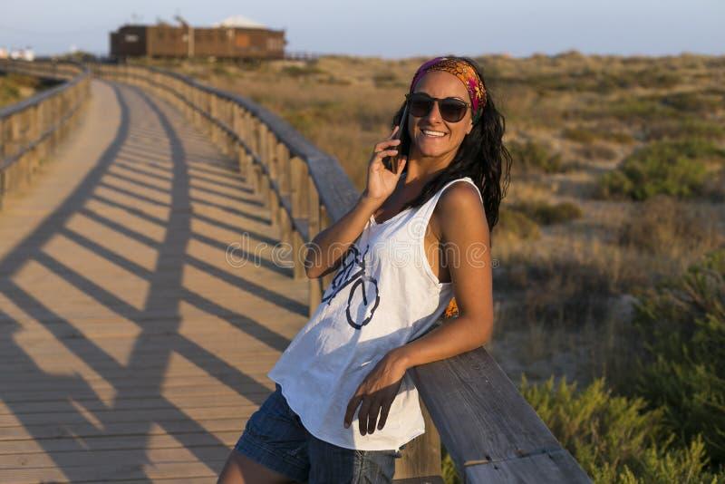 Stående av en ung härlig kvinna som talar på hennes mobiltelefon och le Solnedg?ng Sommar, gyckel och livsstil royaltyfri bild