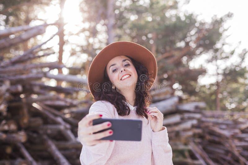 Stående av en ung härlig kvinna som tar en bild med det fria och att le för mobiltelefon Suddig trästambakgrund royaltyfri foto