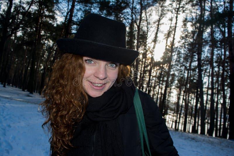 Stående av en ung härlig le europeisk flicka för rött hår i vinterskog arkivbilder