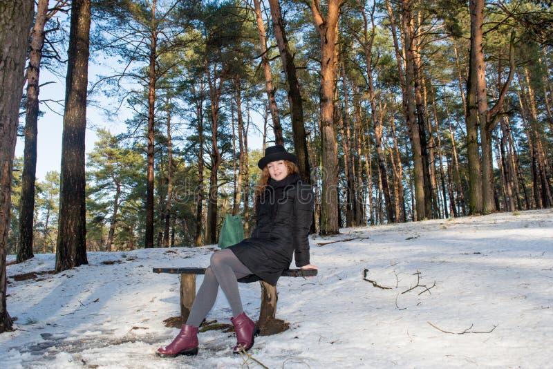 Stående av en ung härlig le europeisk flicka för rött hår som bär sammanträde för svart hatt på bänk i skog fotografering för bildbyråer