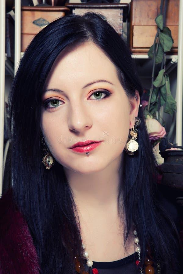 Stående av en ung härlig polsk flicka med gröna ögon som är iklädda en korsett mot bakgrunden av en tappningkaffekvarn royaltyfria foton