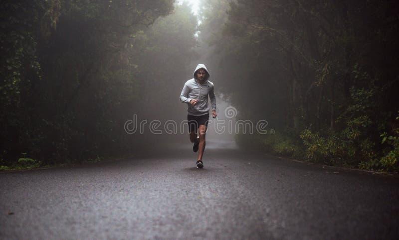Stående av en ung idrottsman nenspring på vägen arkivfoto