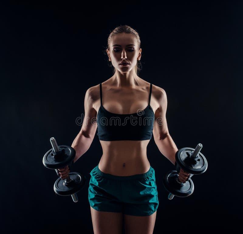 Stående av en ung konditionkvinna i sportswearen som gör genomkörare med hantlar på svart bakgrund Brunbränd sexig idrotts- flick royaltyfria foton