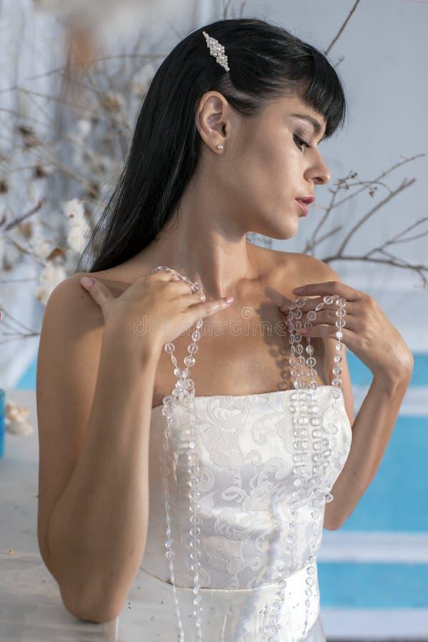 Stående av en ung kvinna i en bröllopsklänning på en suddig bakgrund royaltyfri fotografi