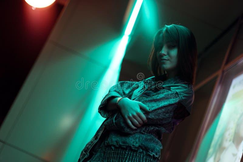 Stående av en ung kvinna i ett grov bomullstvillomslag Brunett med starka ögon Isolerade f?rgbilder p? svart bakgrund fotografering för bildbyråer