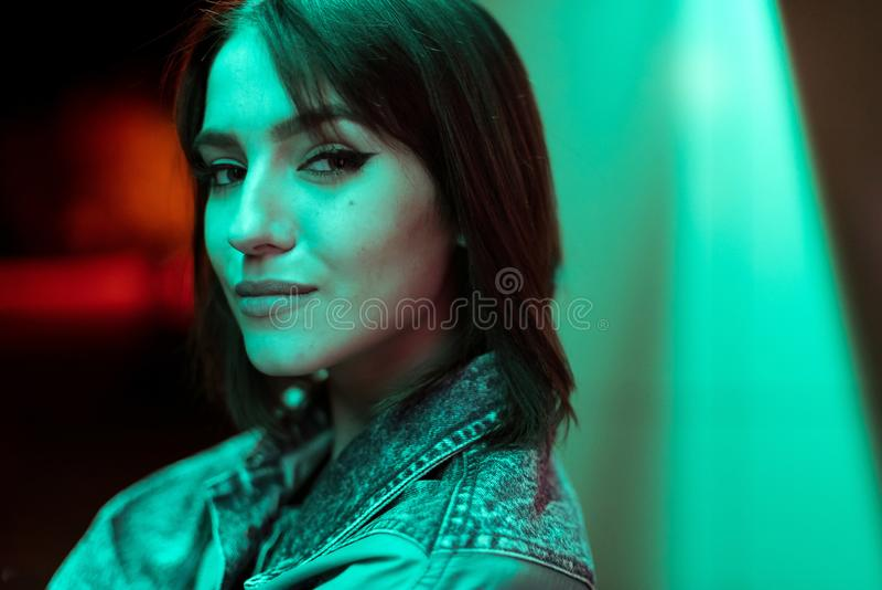Stående av en ung kvinna i ett grov bomullstvillomslag Brunett med starka ögon Isolerade f?rgbilder p? svart bakgrund arkivfoto
