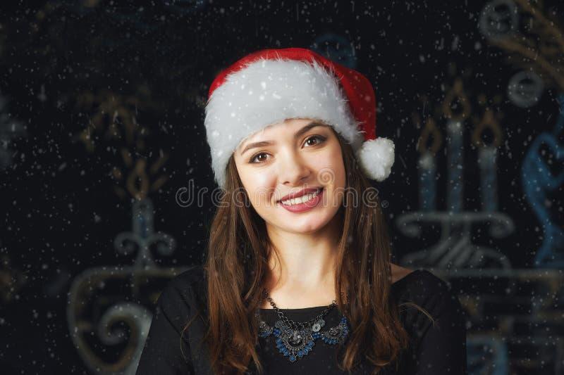 Stående av en ung kvinna i ett lock av Santa Claus på julbakgrund royaltyfri foto
